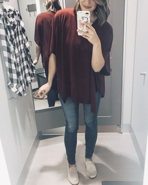 red poncho, jeans, and slip on sneakers