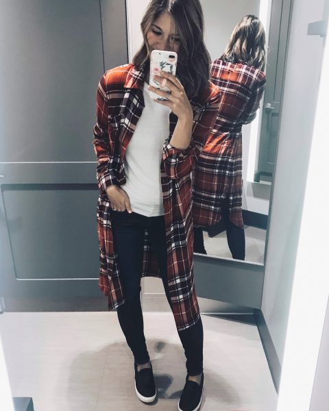 red flannel midi dress styled as a shirt over white long sleeve tee with black slip on sneakers