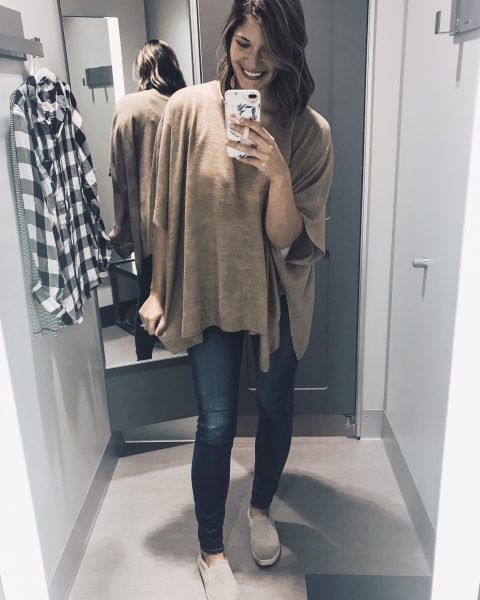 camel poncho, jeans, and slip on sneakers