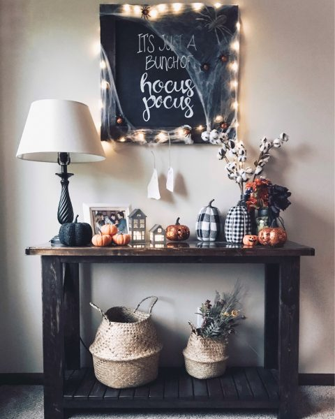 hocus pocus chalkborad with spider webs and twinkle lights over hallween console table