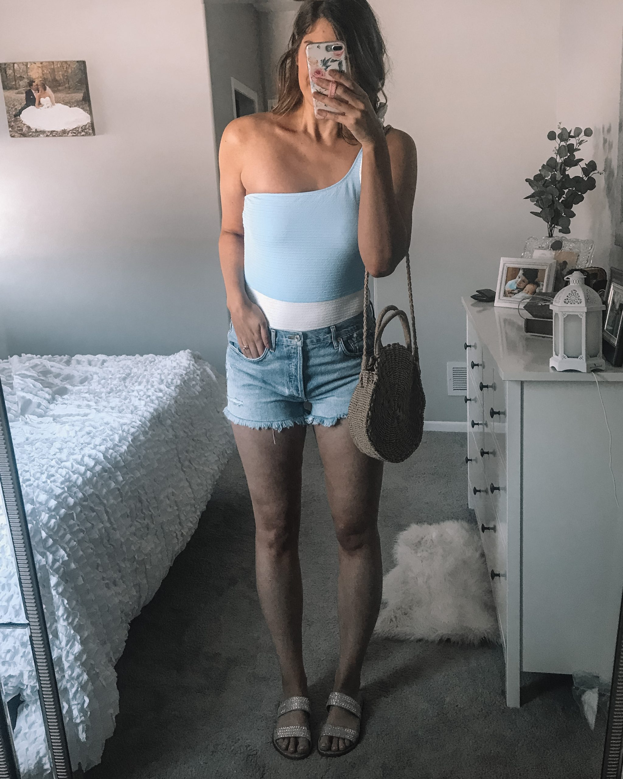 blue and white one shooulder one piece swimsuit with agolde parker denim shorts and straw crossbody bag with rhinestone slide sandals
