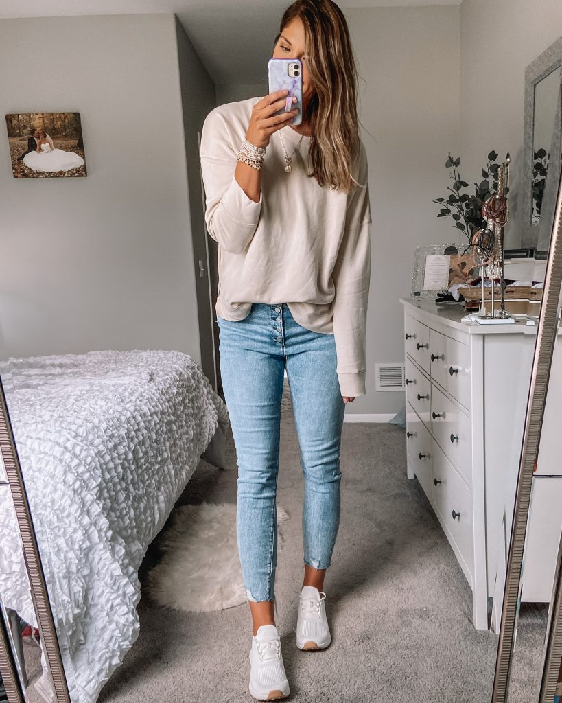 beige $11 walmart sweatshirt / five button front light wash long abercrombie jeans /  white and gold memory foam athletic shoes
